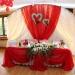 Оформление стола молодоженов красной тканью и сердцами